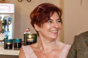 Na zdjęciu Małgorzata Tomala, opiekun Pracowni Plastycznej VINCI. Uśmiechnięta, krótkie kasztanowe włosy. Różowe ramiączka koronkowej sukienki. Za nią na kontuarze stoją trzy różnej wielkości świece w szklanych słojach, w ciemnym kolorze.