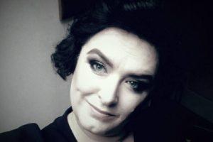 Na zdjęciu instruktorka Katarzyna Szybisty, uśmiechnięta brunetka, krótkie kręcone włosy.
