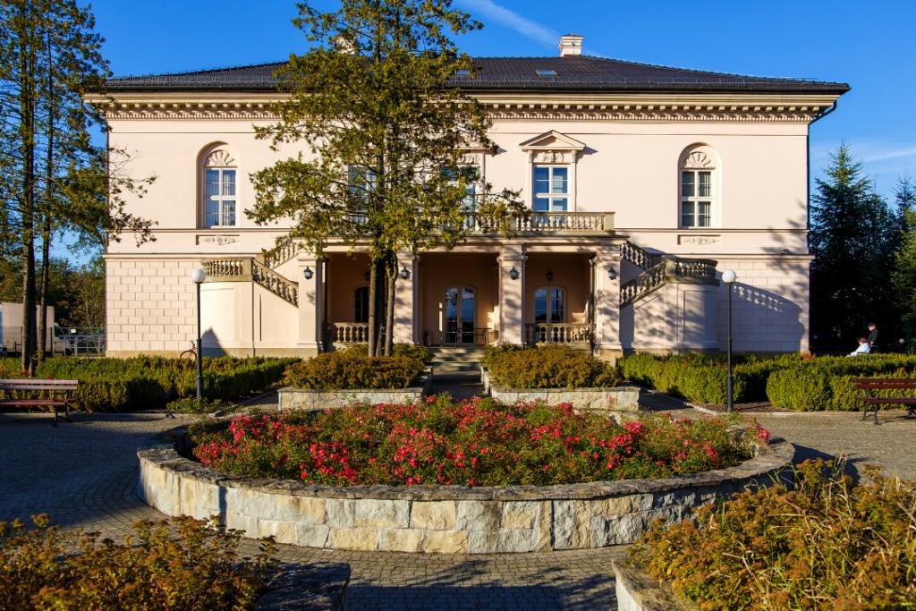 Zdjęcie Dworu Dzieduszyckich w Radziszowie i ogrodu dworskiego. Na piewrszym planie ogród. Na drugim budynek dworu z arkadami.