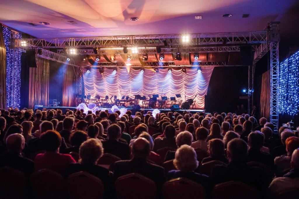 Zdjęcie z koncertu noworocznego SkaVienna, ujęcie z tyłu sali na scenę. Sala oświetlona reflektorami i girlandami światełek, ściany pokryte czarną i złotą tkaniną. Na scenie pulpity i krzesła dla orkiestry. Widzowie siedzą.