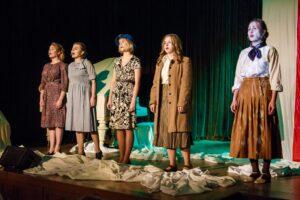 """Scena teatralna w Pałacyku """"Sokół"""". Na scenie białe tkaniny udrapowane na podłodze, w tle po prawej zawieszona pionowo flaga biało-czerwona, po lewej biały fortepian. Stonowane światło, z zielonym efektem. Na scenie stoją wokalistki zespołu Tanto: 5 dziewczyn ucharakteryzowanych w stylu lat 40-tych (sukienki midi, podkreślające talię, stonowane kolory). Jedna z dziewcząt w niebieskim kapeluszu, inna w brązowym płaszczu."""