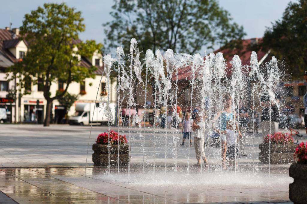 Zdjęcie fontanny na rynku w Skawinie. Na pierwszym planie tryskające w górę strumienie wody, W tle drzewa i zabudowania wokół rynku.